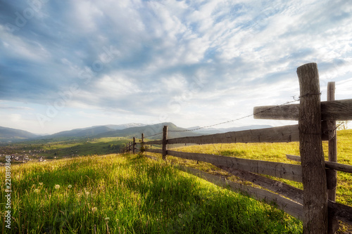 Spoed Foto op Canvas Grijze traf. amazing mountain view. wooden fence and high mountain village. summer landscape. beautiful natural background