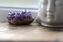 Purple And Gemmy Amethyst Stone With White Buddha Head On The Windowsill Background. Rough Ametist Crystals On Home Altar, Spiritual Ritual Meditation Place. Religion Symbol