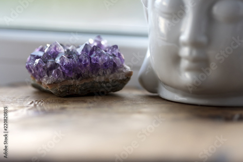 Purple and gemmy amethyst stone with White Buddha head on the windowsill background Canvas Print
