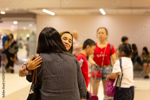 Happy daughter hugging mother on arrival at the airport. Canvas Print