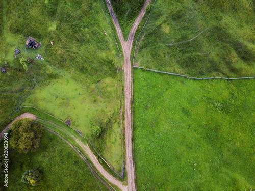 arial veiw of rural road, green field and trees. drone shot