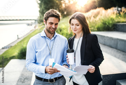 Fotografia, Obraz  A young businessman and businesswoman with coffee talking outdoors at sunset