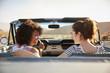 Two Female Friends Enjoying Road Trip In Open Top Classic Car