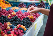Marketplace With Different Fruits. Seller's Hand On Colorful Berry Background Outdoors. Sale, Shopping And People Concept. Close Up Buying Berry At Street Food Market. Selective Focus.