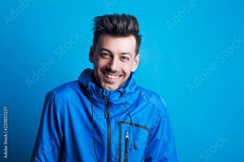 Portrait of a young laughing man in a studio with anorak on a blue background Canvas Print