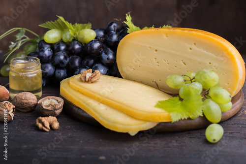 Dutch hard cheese Maasdam or Emmentaler, cheese with holes and white hard goat cheese with grape honey and nuts