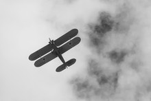 Black And White Photo Of Biplane On Airshow In Krakow, Poland. Historical War Plane, With Stars On Wings, Monochrome Design.