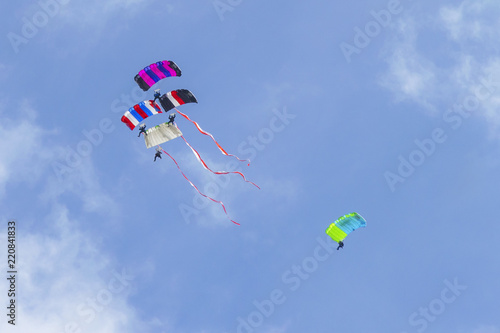 Foto op Canvas Luchtsport Four parachutists with colorful parachutes, Poland national flag colors wawing behind on airshow. Artists team work, cooperation. Parachuters paragliding sky performance.