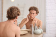 Young man looking in mirror after shaving at home
