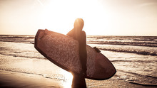 Man With Surfboard At Sunset