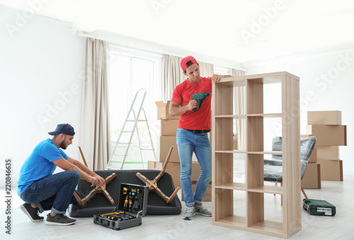 Fotografie, Tablou Male movers assembling furniture in new house