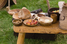 Typical Selection Of Medieval Food Including Bread, Butter, Cheese, Fruit And Nuts Served In Wooden Bowls Or Trenchers