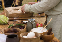 Medieval Food Preparation Including Bread, Butter, Cheese, Fruit In Wooden Bowls Or Trenchers