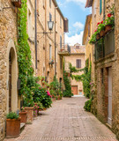 Fototapeta Panels - A narrow and picturesque street in Pienza, Tuscany, Italy.