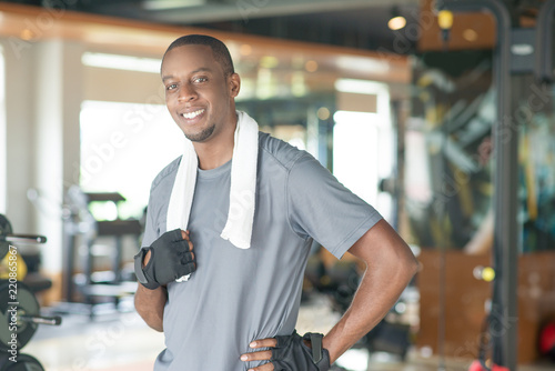 Smiling sporty black man wearing towel around neck and looking at camera. Young guy wearing t-shirt and relaxing in gym. Workout and break concept. Front view.