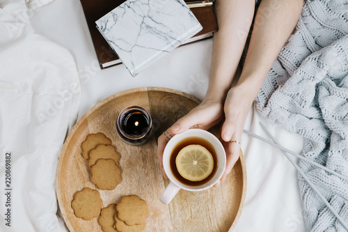 Fotografia  Cozy flatlay of woman's hands holding cup of lemon tea in bed with knitted sweat