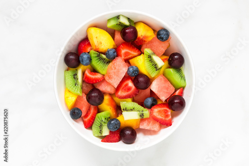 Montage in der Fensternische Fruchte Bowl of healthy fresh fruit salad on white marble background. healthy food