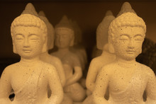Many Identical Buddha Statuettes Stand On The Shelf In The Store.