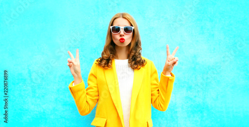 Fotografia  Fashion portrait woman sends an air kiss in a yellow coat posing on a blue backg