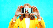 Woman Takes Picture Self Portrait On Smartphone On Colorful Blue Background