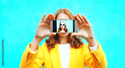 woman takes picture self portrait on smartphone on colorful blue background Canvas-taulu