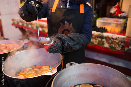 Hot gluhwein or mulled wine in a cauldron at fair, local treat, warm and spicy. A hot wholesome traditional citrus drink on fair. Vitamins in the winter festival. Pour the drink into a glass or a cup.