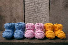 Baby Concept: Different Colored Baby Booties, Three Pairs Of Baby Booties On A Wooden Background