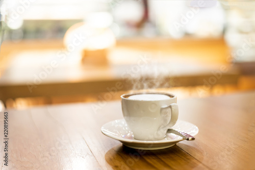 Fotografering  Hot cup of coffee or hot cappuccino on wooden table at coffee shops in blurry ba
