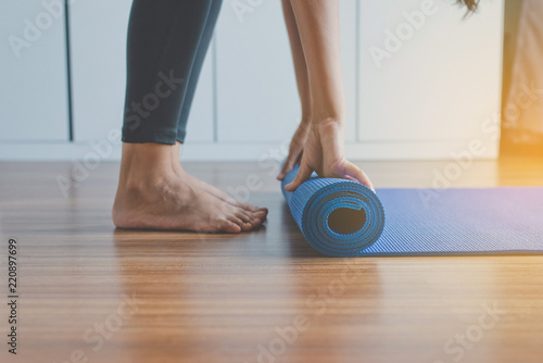 Tuinposter Ontspanning Exercise equipment,Woman hand rolling or folding yoga mat after a workout,Healthy fitness and sport concept