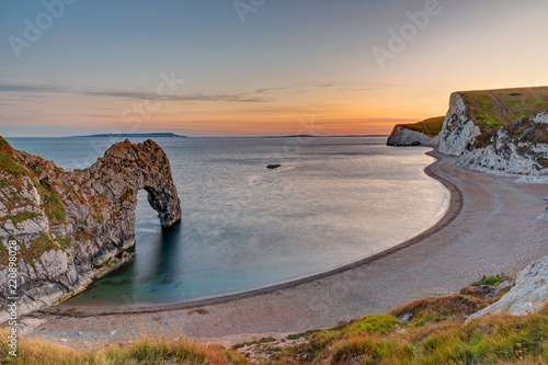 Photo  The natural arch Durdle Door at the Jurassic Coast in England at sunset