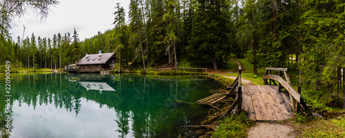Photo Wonderful emerald-colored lake with wooden bridge and cabin near Cortina d'Ampez