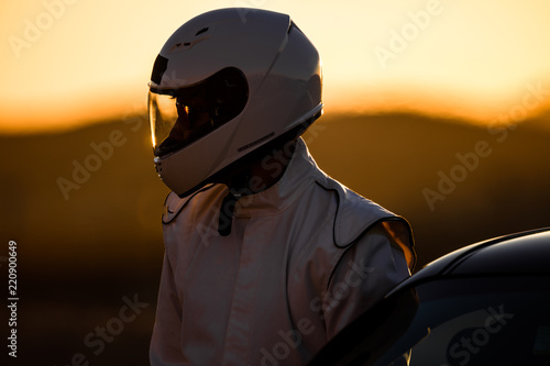 In de dag F1 A Helmeted Driver Preparing To Race At Sunrise