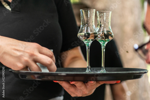 Fotografie, Obraz Two glasses of liquor or grappa on a plate served in a german biergarten of a vi