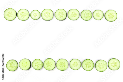 Cucumber slices forming a frame on a white background with copyspace