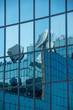 Satellite dishes reflected on the glass wall of a modern office building