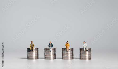 Fototapeta Miniature people sitting on piles of coins. A concept about social costs. obraz
