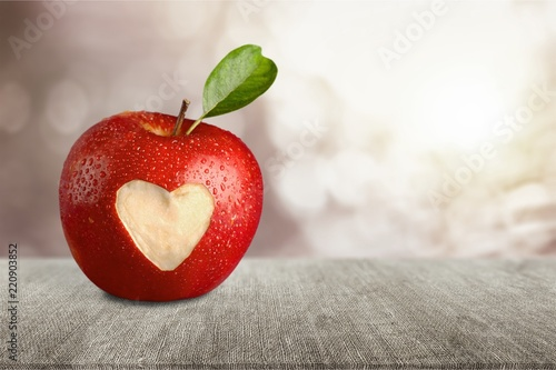 Red apple with a heart shaped cut-out on backgrouund