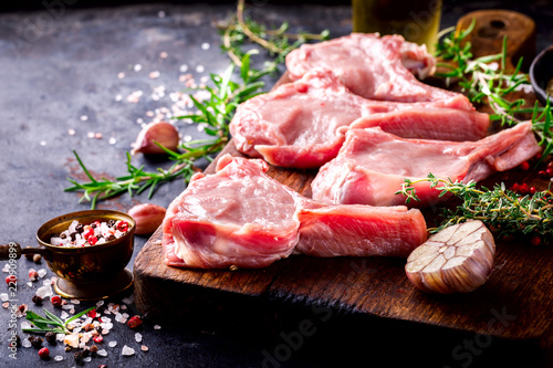 Staande foto Vlees Meat Raw Fresh Mutton on the bone Spices Chesno and Rosemary on a black background Copy space for Text
