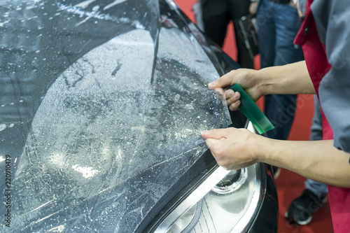 Worker install car paint protection film with spatula Wallpaper Mural