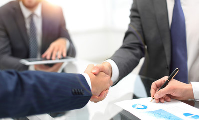 Fototapeta Men shaking hands with smile at office with their coworkers.