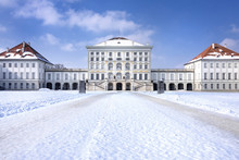Germany, Bavaria, Munich, Nymphenburg Palace: Panorama View Of Winter Scene With Main Building Entrance Of The Famous Castle, White Icy Snow, Blue Sky In The Bavarian Capital.