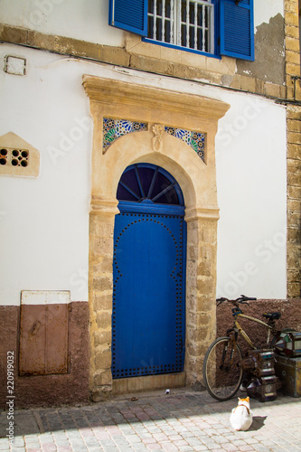 Staande foto Afrika The old wooden door is blue in the background of the plastered peeling wall. Moroccan style. Africa, Morocco, Essaouira