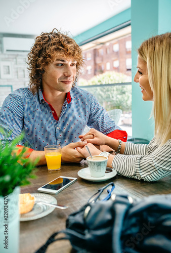 Photo  Young man and woman holding hands at a cafe