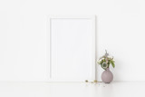 Elegant white a4 portrait frame mockup with dried field wild flowers in vase on white wall background. Empty frame, poster mock up for presentation design