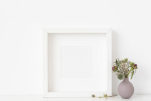 White Square Portrait Frame Mockup With A Small Bouquet Of Dried Flowers In A Lilac Small Vase On White Wall Background. Empty Frame, Poster Mock Up For Presentation Design.