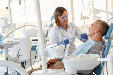 Fototapeta Dentist in dental office talking with male patient and preparing for treatment.