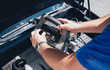 Accumulator charging. Hands and terminal. Car repair.