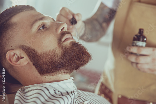 Photo The barber applies the beard oil with a dropper