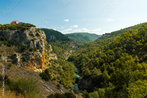 Beautiful top view of a lonely and cute house in a mountain cliff next to the river Jucar in Cuenca, Spain. Nature landscape on a sunny day.