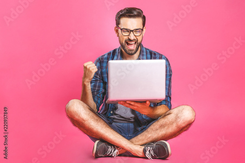 Obraz Online working concept. Casual business man relaxed working and browsing internet on laptop computer. Freelance sitting and typing on laptop keyboard at home office. Pink background. - fototapety do salonu
